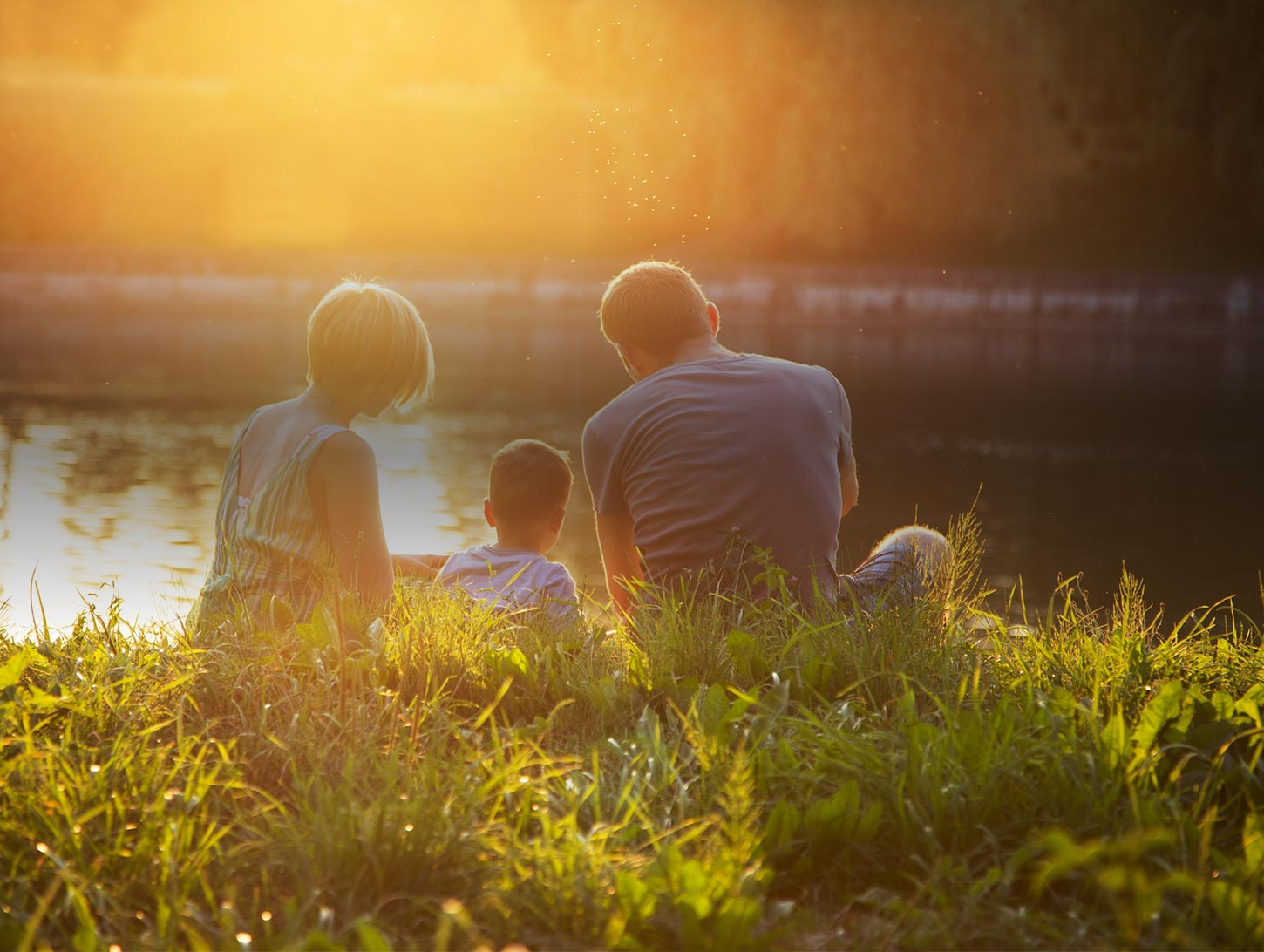 A family sits by a lake at sunset